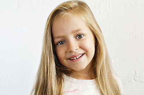 happy little girl with long blonde hair at a Preschool & Daycare Serving New Braunfels, TX