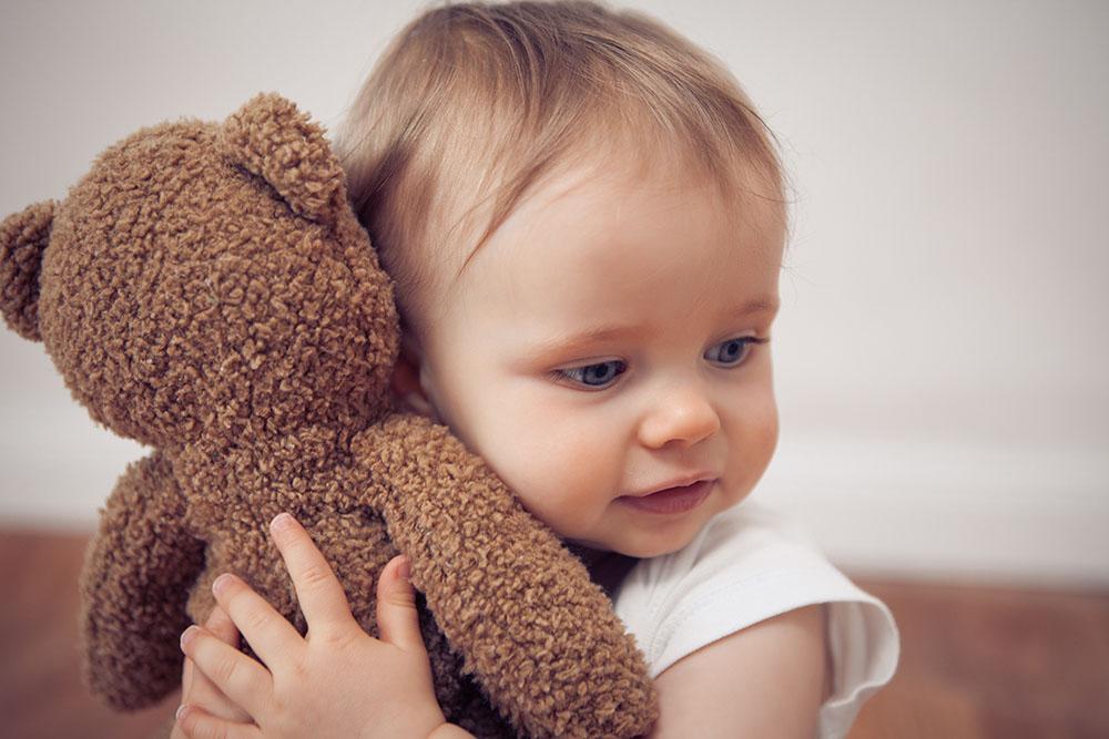 happy toddler cuddling stuffed animal at a Preschool & Daycare Serving New Braunfels, TX