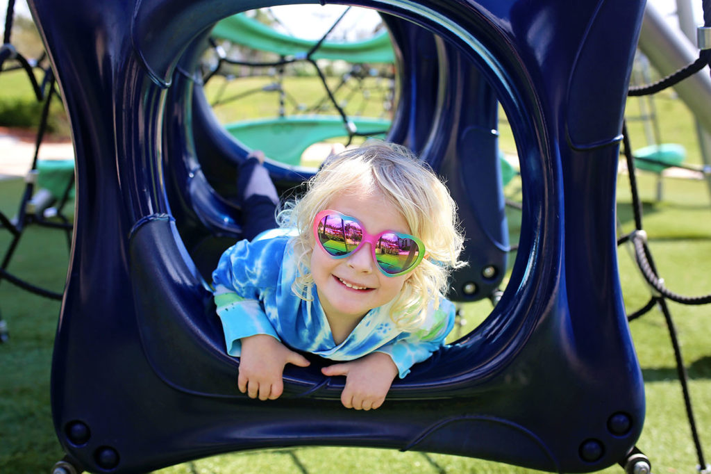 Girl With Sunglasses Smiling at the Playground at a Preschool & Daycare Serving New Braunfels, TX