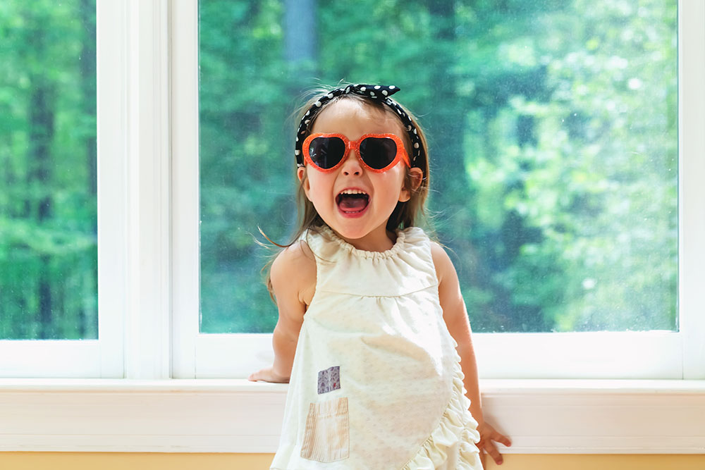 Happy toddler girl wearing sunglasses at a Preschool & Daycare Serving New Braunfels, TX