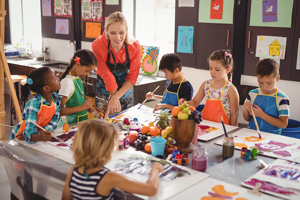 Teacher assisting schoolkids in drawing class at a Preschool & Daycare Serving New Braunfels, TX