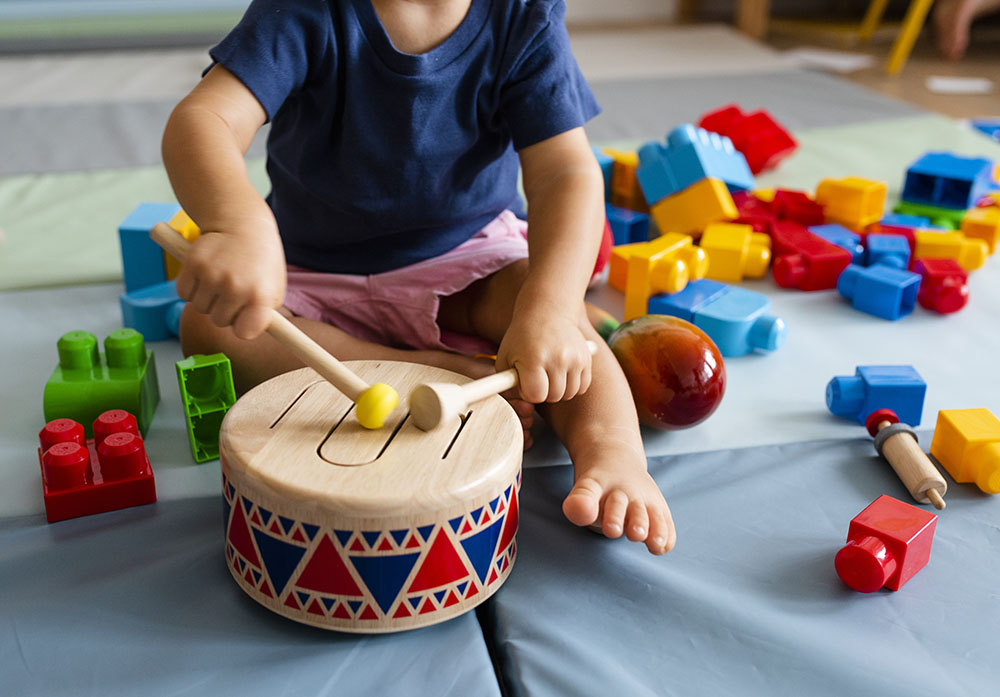 baby playing with drums at a Preschool & Daycare Serving New Braunfels, TX