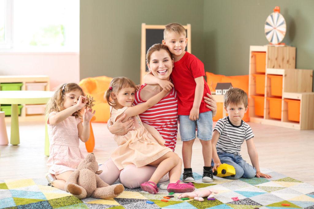 Nursery teacher with cute little children in kindergarten at a Preschool & Daycare Serving New Braunfels, TX
